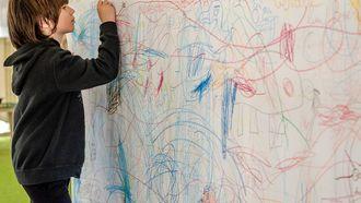 Kind dat creatief bezig is met tekenen op de muur