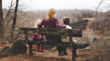 moeder en kinderen zitten op een bankje in de rustige natuur