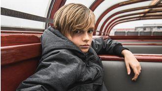 kind puber in de puberteit op een boot kijkt chagrijnig