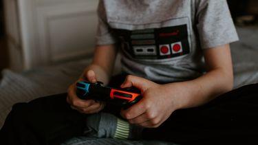 gamen / kind met gameboy op bed