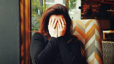 Moeder die haar handen voor haar gezicht houdt omdat ze zich schaamt voor wat haar kind zei
