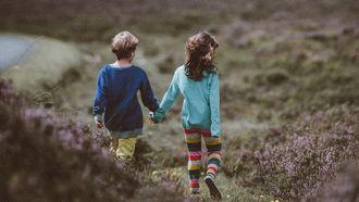 Een beste vriend en beste vriendin die kind zijn en hand in hand van een heuvel aflopen