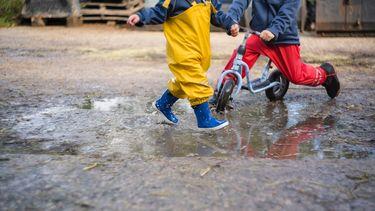 Kinderen die buiten spelen met laarzen in de plassen