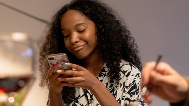 Puberdochter die aan tafel op haar telefoon zit