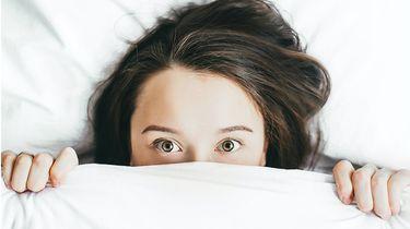 jeugdpuistjes / meisje ligt onzeker onder haar dekbed