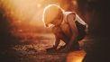 Gevoelig kind dat in de zon met wat zand speelt