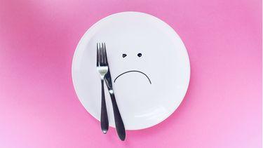 eetstoornis bij pubers / bord met verdrietig gezicht