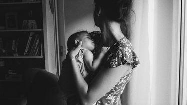Moeder die haar baby vasthoudt en de andere kantop kijkt