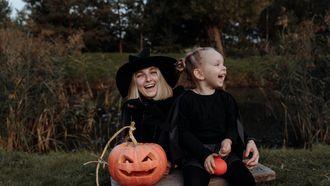 Moeder en dochter verkleed als heksen met pompoenen voor halloween die griezelfilms gaan kijken