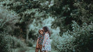 Twee kinderen die dankbaar zijn en elkaar knuffelen