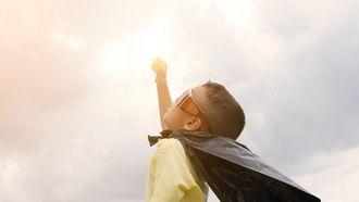 Kind dat met een plastic cape de wereld te hulp schiet om het probleem van plasticvervuiling op te lossen