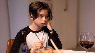 Een puberzoon aan tafel met zijn hand onder zijn kin