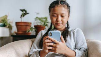 sociale media / meisje zit op de bank met telefoon
