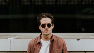 mentale gezondheid / man met zonnebril leunt tegen muur