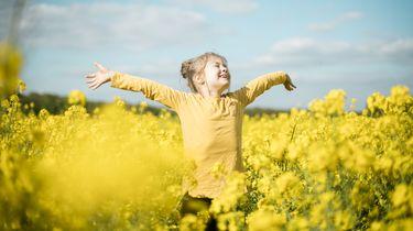 een kind die gelukkig door een veld bloemen danst in haar lievelingskleur