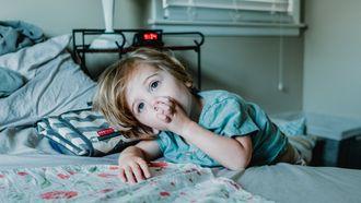 Kind duimend op bed, dat het afleren moeilijk vind