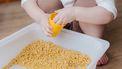Kind dat sensopathisch aan het spelen is met macaroni