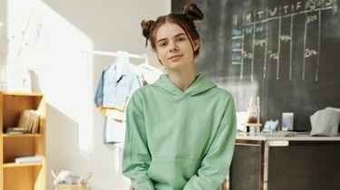 puberteit / meisje zit op een stoel in groene trui