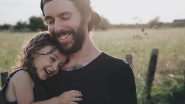 Meisje dat aan het knuffelen is met haar vader