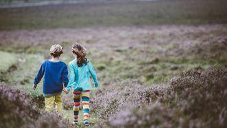 Een jongen en een meisje die hand in hand lopen omdat een ouder zijn zoon feministisch heeft opgevoed