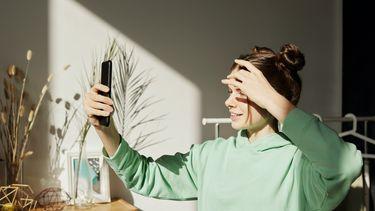 Meisje maakt een selfie met haar telefoon - waarom tieners online communiceren