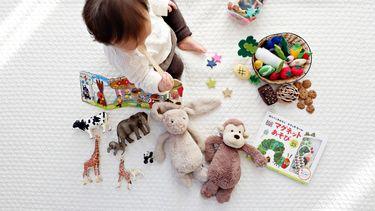 kind speelt met zijn kalmeer kit op een kleed