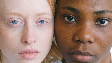 Een wit meisje en zwart meisje dat samen tegen racisme strijden