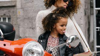 Jonge moeder met haar dochter op een scooter die een tong uitsteken naar de spiegel