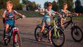 Drie jongetjes die nog te jong zijn om alleen te fietsen