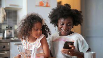 Moeder die met haar dochter op schoot zit en apps voor ouders gebruikt